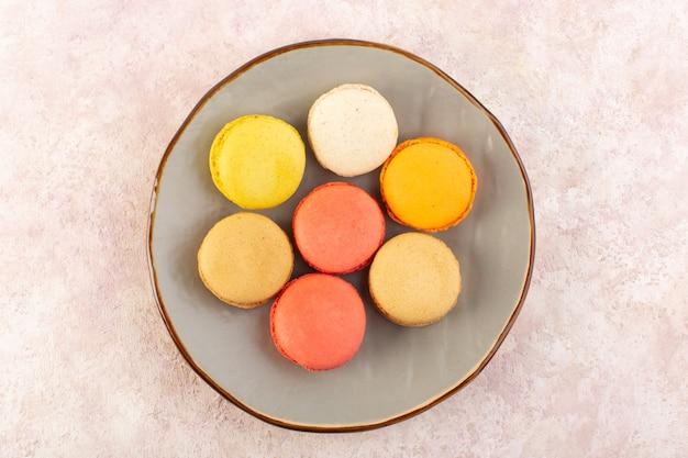 Eine bunte französische macarons der draufsicht innerhalb der platte auf dem rosa schreibtischzuckerkuchenkeks süß