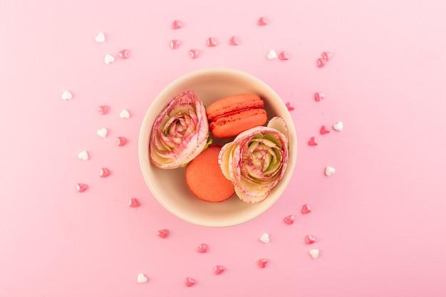 Eine bunte französische macarons der draufsicht mit blumen auf dem rosa schreibtischkuchen-kekszuckersüß