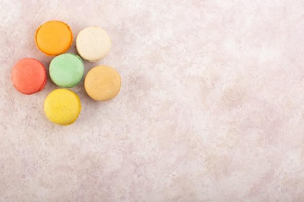 Eine bunte französische macarons der draufsicht rund geformt und köstlich auf dem rosa schreibtischkuchenzuckersüß
