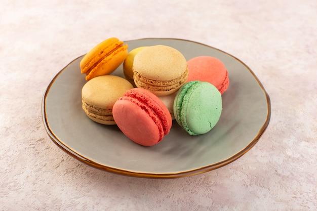 Eine bunte französische macarons der vorderansicht innerhalb der platte auf dem süßen schreibtischkuchen des rosa schreibtischkekszuckers