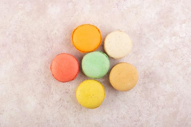 Eine bunte französische macaronsrunde der draufsicht bildete köstlich auf dem rosa schreibtischkuchen-kekszuckersüß