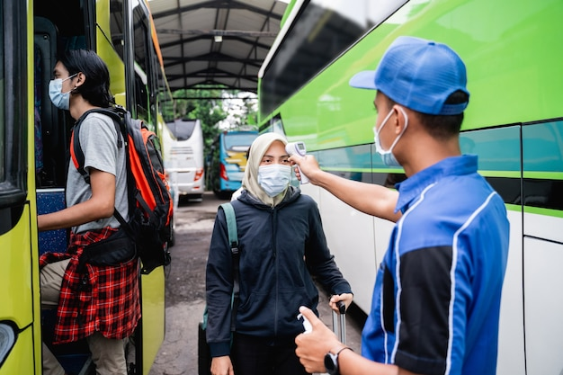 Eine busbesatzung in uniform und ein hut mit einer thermopistole inspizieren den passagier einer frau in schleier und maske, bevor sie in den bus einsteigen