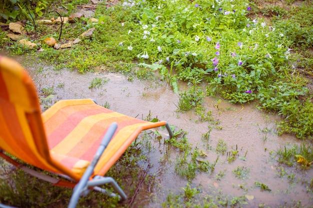 Eine chaiselongue steht in einem garten mit blumen in einer pfütze von der fallenden regenherbstsaison in