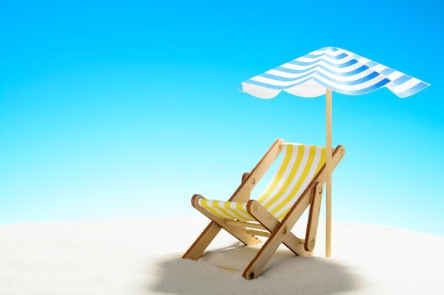 Eine chaiselongue unter einem sonnenschirm am sandstrand mit kopierraum