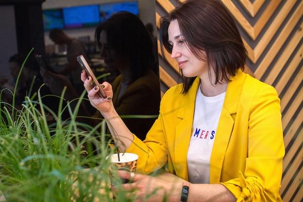 Eine charmante frau liest gute nachrichten auf einem handy, während sie sich in einem café entspannt