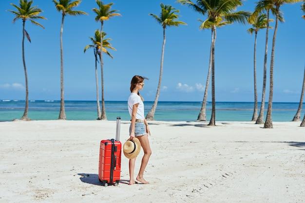 Eine charmante frau mit einem roten koffer auf einer insel