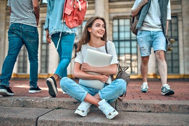 Eine charmante studentin mit rucksack und laptop sitzt auf den stufen in der nähe des campus vor dem hintergrund vorbeikommender studenten.