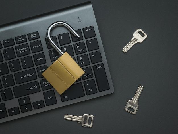 Eine computertastatur, ein offenes schloss und drei tasten auf dunkelgrauem hintergrund. das konzept der computersicherheit. flach liegen.