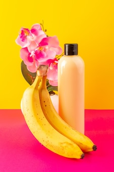 Eine cremefarbene flasche plastikshampoo-dose der vorderansicht mit schwarzer kappe, die mit bananen auf dem rosa-gelben hintergrundkosmetik-schönheitshaar isoliert wird
