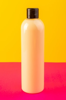 Eine cremefarbene flasche plastikshampoo-dose der vorderansicht mit schwarzer kappe lokalisiert auf dem rosa-gelben hintergrundkosmetik-schönheitshaar