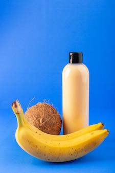 Eine cremefarbene plastik-shampoo-dose der vorderansicht mit schwarzer kappe, die zusammen mit kokosnuss und bananen auf dem schönheitshaar der blauen hintergrundkosmetik isoliert wird