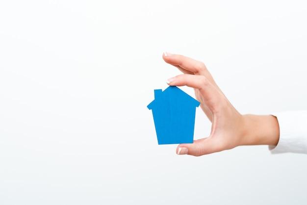 Eine dame, die im business-outfit nach hause hält und die möglichkeit bietet, ihre eigene immobilie zu besitzen. hauskauf oder umzug neuer versicherungen oder hypothekenkonzepte, die von der jungen geschäftsfrau gezeigt werden.