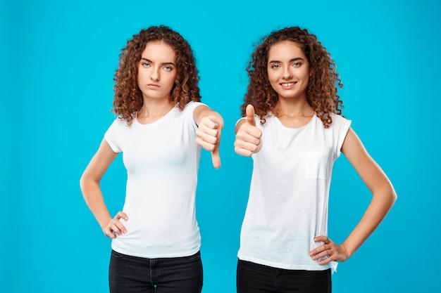 Eine der zwillingsschwestern zeigt abneigung, eine andere wie über blau.