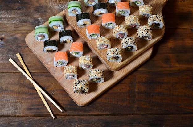 Eine detaillierte aufnahme einer reihe von japanischen sushi-rollen und ein gerät für ihre verwendung essstäbchen