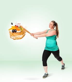 Eine dicke frau, die mit einem schläger einen süßen kuchen zertrümmert. ungesundes essen. das konzept der diät und des gesunden lebensstils für dicke frauen