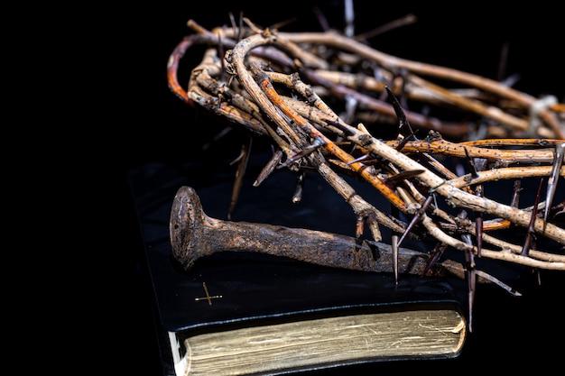 Eine dornenkrone und ein nagel liegen im dunkeln auf dem buch der bibel. das konzept der karwoche.