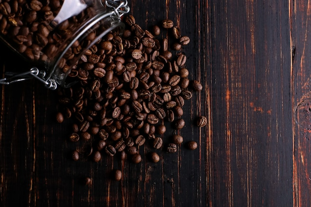 Eine dose kaffee, zerstreute körner auf einem holztisch.