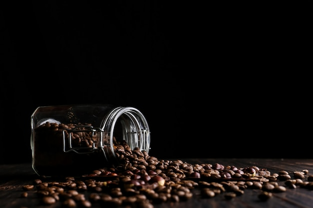 Eine dose kaffee, zerstreute körner und schwarze schokolade auf einem holztisch.