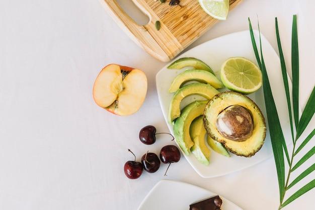Eine draufsicht auf avocado; apfel und kirschen auf weißem hintergrund