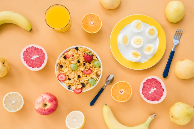 Eine draufsicht auf bananen; grapefruit; orange; birnen; saft; gekochte eier und cornflakes auf braunem hintergrund