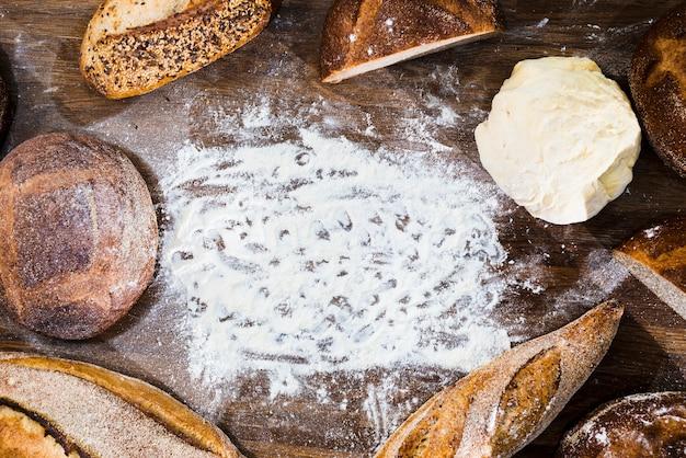 Eine draufsicht auf brot; stangenbrot und gekneteter teig mit mehl auf hölzernem schreibtisch