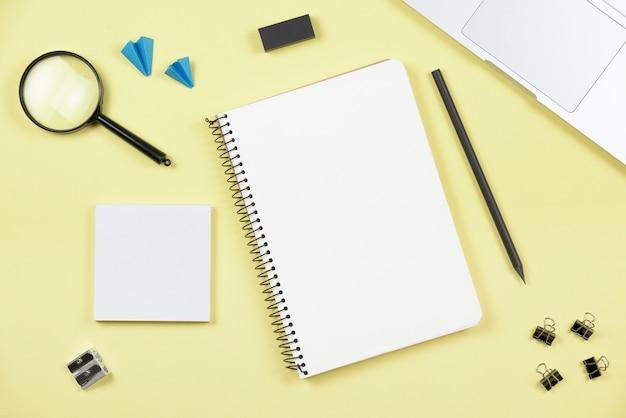 Eine draufsicht auf büroartikel mit laptop auf gelbem hintergrund