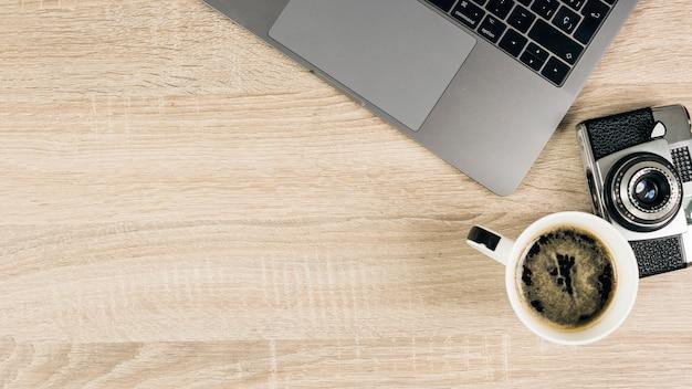 Eine draufsicht auf den laptop; kamera und kaffee auf holztisch