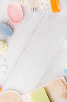 Eine draufsicht auf den schwamm; kräuter seife; serviette; handschuhe; massagebürste; luffa und blume auf holzbrett mit platz für das schreiben von text