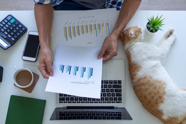 Eine draufsicht auf die hand eines mannes auf einem schreibtisch schreibt gewinn- und verlustdiagramme auf dem laptop zu hause. freiberufler arbeiten zu hause. work-from-home-konzept