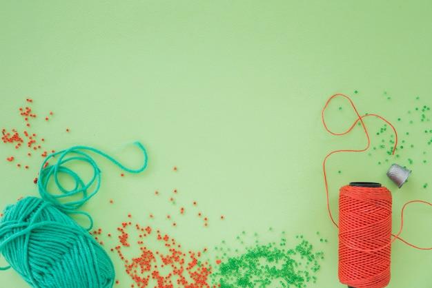 Eine draufsicht auf eine zange; schere; perlen und spule auf grünem hintergrund