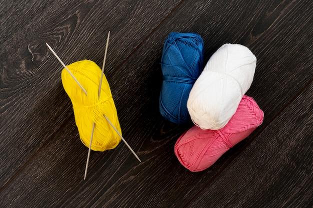 Eine draufsicht auf einige garnrollen mit auf dem tisch eingesetzten stricknadeln