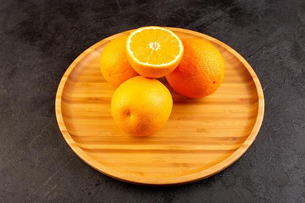 Eine draufsicht auf frische orangen sauer reif ganz und geschnittenes weiches zitrusvitamingelb auf dem dunklen schreibtisch