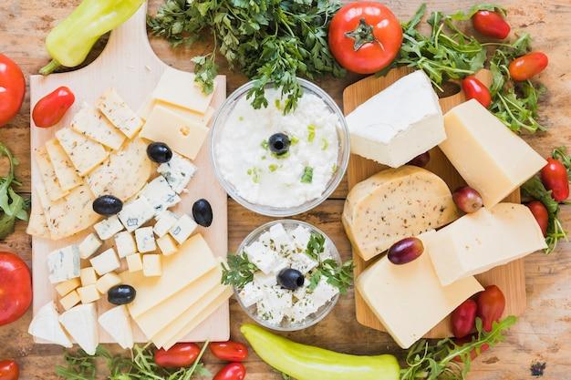 Eine draufsicht auf frischkäseplatte mit oliven; petersilie; tomaten und rucola blätter auf schreibtisch aus holz