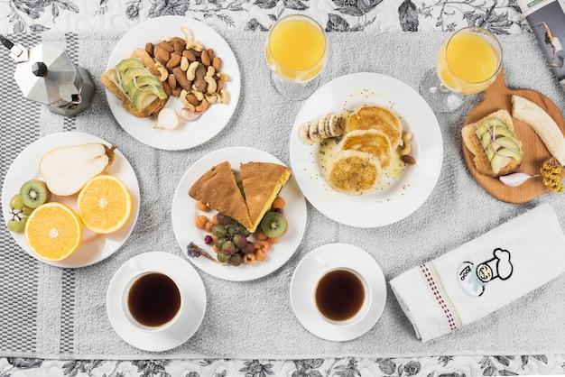 Eine draufsicht auf früchte; sandwiches; pfannkuchen; kuchen auf teller über serviette