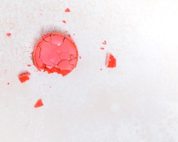 Eine draufsicht auf gebrochenen rosa cupcake auf strukturierten hintergrund