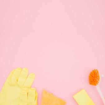 Eine draufsicht auf handschuhe; bürste; schwamm und flasche auf rosa hintergrund