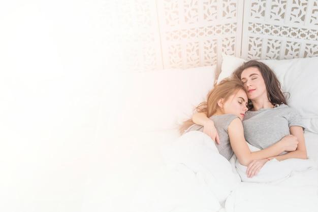Eine draufsicht auf junge lesbische paare, die auf bett schlafen
