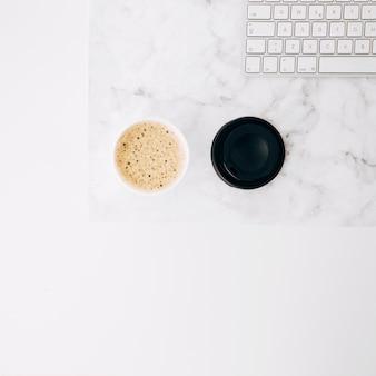 Eine draufsicht auf kaffee wegwerfbare mitnehmerkaffeetasse und -tastatur auf weißem schreibtisch