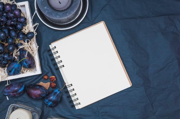 Eine draufsicht auf kerzen; leerer gewundener notizblock; pflaumen und trauben auf textilem hintergrund