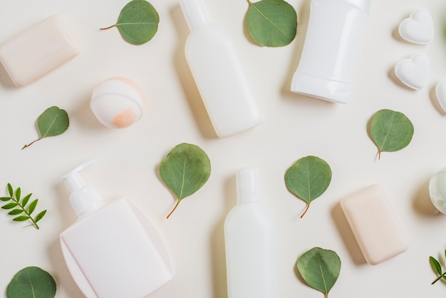 Eine draufsicht auf kosmetikprodukte; seife; badebombe und grüne blätter
