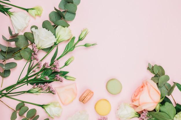 Eine draufsicht auf makronen mit frischer rose; limonium und eustoma blumen auf rosa hintergrund