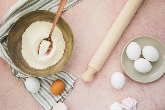 Eine draufsicht auf mehl; eier; nudelholz und serviette auf farbigem hintergrund