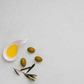 Eine draufsicht auf olive; blätter und öl auf weißem konkretem hintergrund