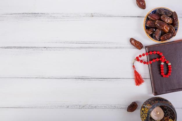 Eine draufsicht auf saftige datteln; brennende kerze; rote gebetsperlen auf tagebuch über weißem schreibtisch