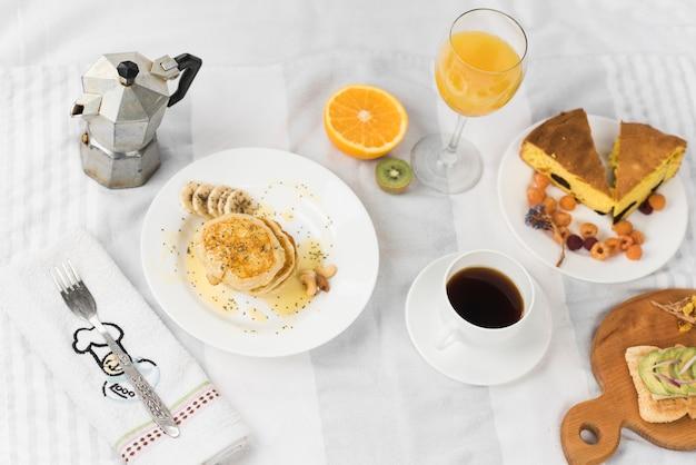 Eine draufsicht auf sandwich; pfannkuchen; saft; früchte; kaffee- und kuchenstück auf tischdecke