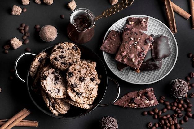 Eine draufsicht auf schokoladenmüsli-plätzchen und -schokolade auf schwarzem hintergrund