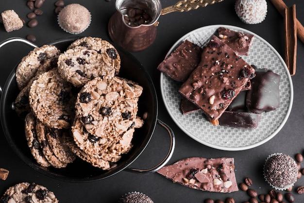 Eine draufsicht auf schokoladenmüsli-plätzchen und -trüffeln auf schwarzem tropfen
