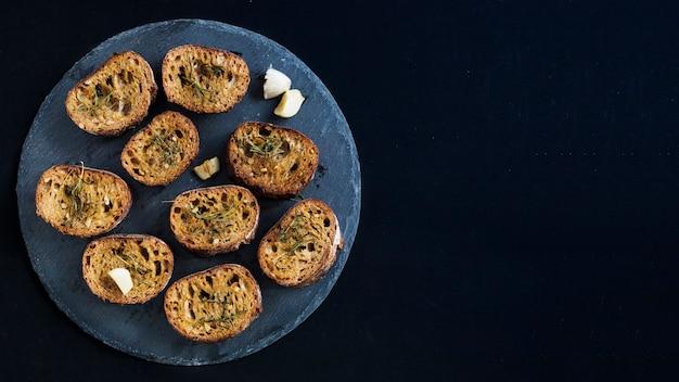 Eine draufsicht auf toast mit rosmarin-toppings auf rundem schiefer vor schwarzem hintergrund