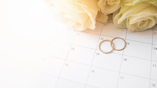 Eine draufsicht auf trauringe am kalendertag mit rosen
