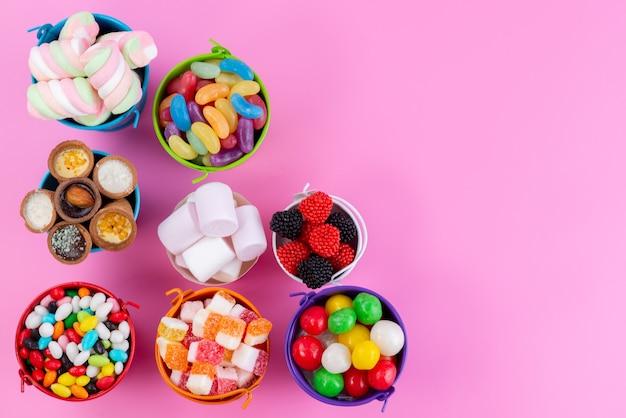 Eine draufsicht auf verschiedene süßigkeiten, wie z. b. marmeladenbonbons in körben auf rosa, zuckersüße farbe